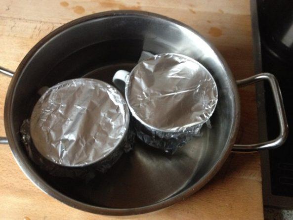 Die beiden Tassen gut mit Alufolie verschließen (ich geb noch Gummiringe drum) und in einen Topf stellen, Wasser einfüllen und zum Kochen bringen. Bei zurück gedrehter Hitze 30 - 35 Minuten stocken lassen.