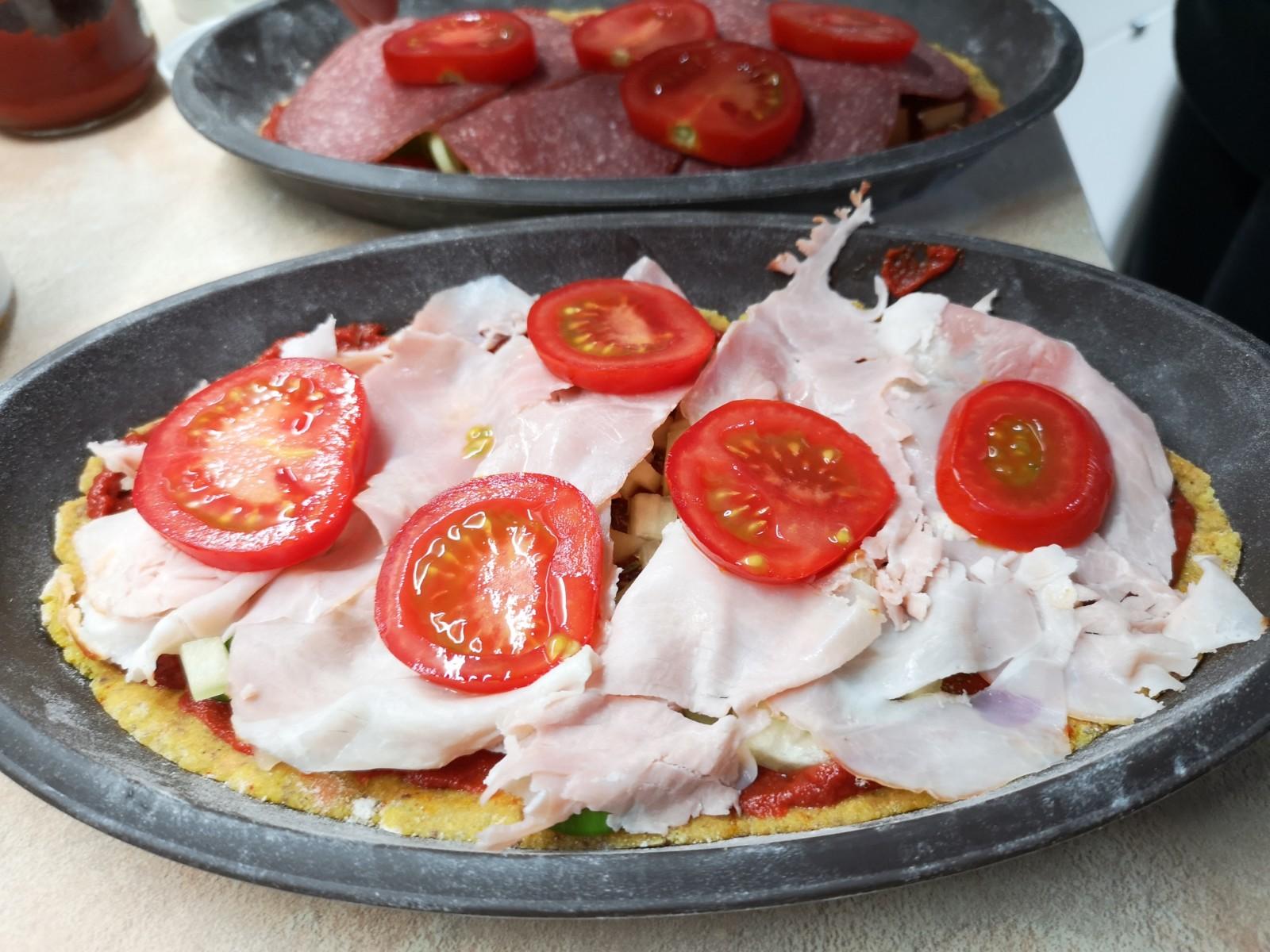 Ketogene Pizza in ovaler Form mit Schinken und Tomate